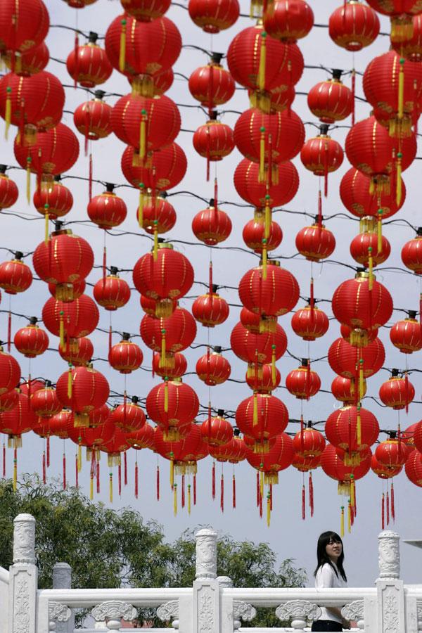 18. Китаянка проходит мимо традиционных китайских фонариков в храме в Куала-ЛУмпур, Малайзия. Этнические китайские малазийцы готовятся праздновать китайский лунный новый год тигра, который в этом году выпадает на 14 февраля. (AP Photo/Lai Seng Sin)