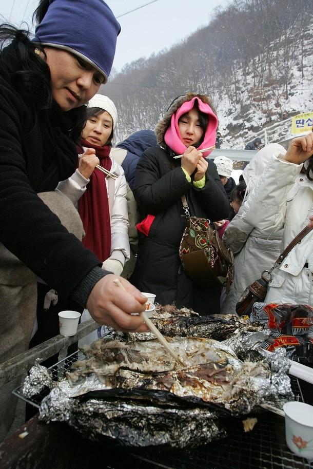 10) Некоторые из любителей рыбы устраивают её дегустацию прямо на озере, они зажаривают её на огне или делают суши. (Chung Sung-Jun/Getty Images)