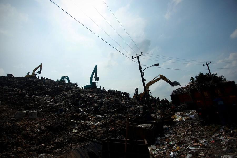 1) Стоящие на горах мусора рабочие рядом с экскаваторами на свалке Бантар Гебанг, одной из самых больших свалок мусора в Индонезии.