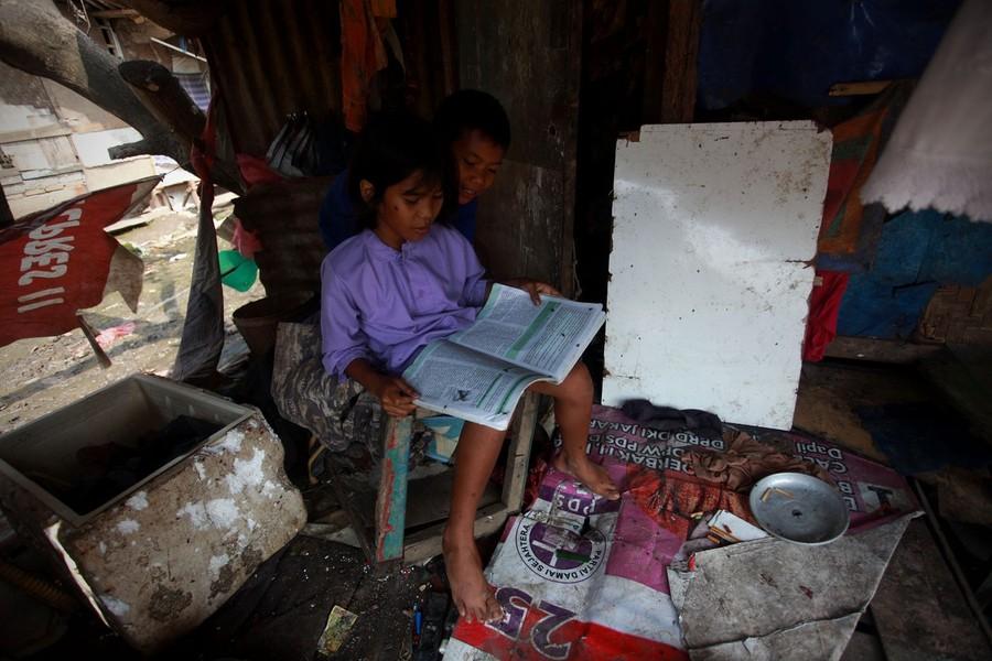 24) 8-летний Басир и 11-летняя Нанг вместе делают домашнее задание после окончания уроков.