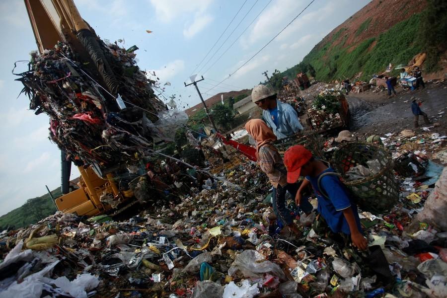 14) Дети работают на свалке наравне с взрослыми. На снимке - 8-летний Басир и 11-летняя Нанг стоят рядом с экскаватором, разгружающем мусор.