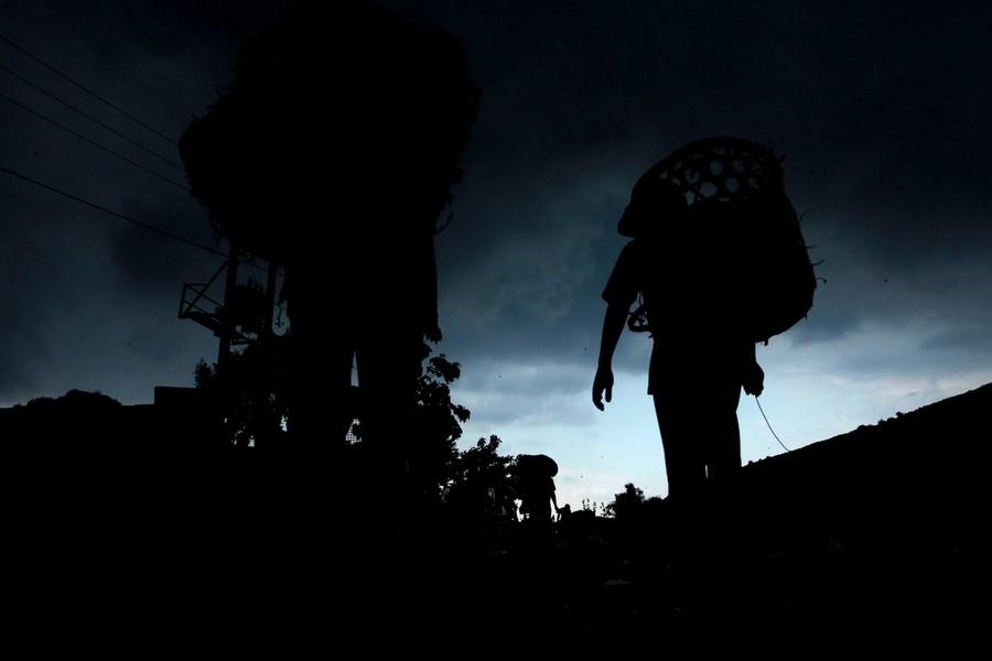 12) Дети возвращаются домой вечером 27 января 2010 года после нескольких часов сбора мусора на свалке.