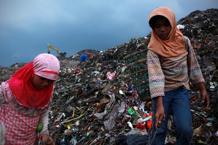 7) Дети разбирают мусор в поисках пластиковой посуды, которую их семьи продают, чтобы прокормиться.