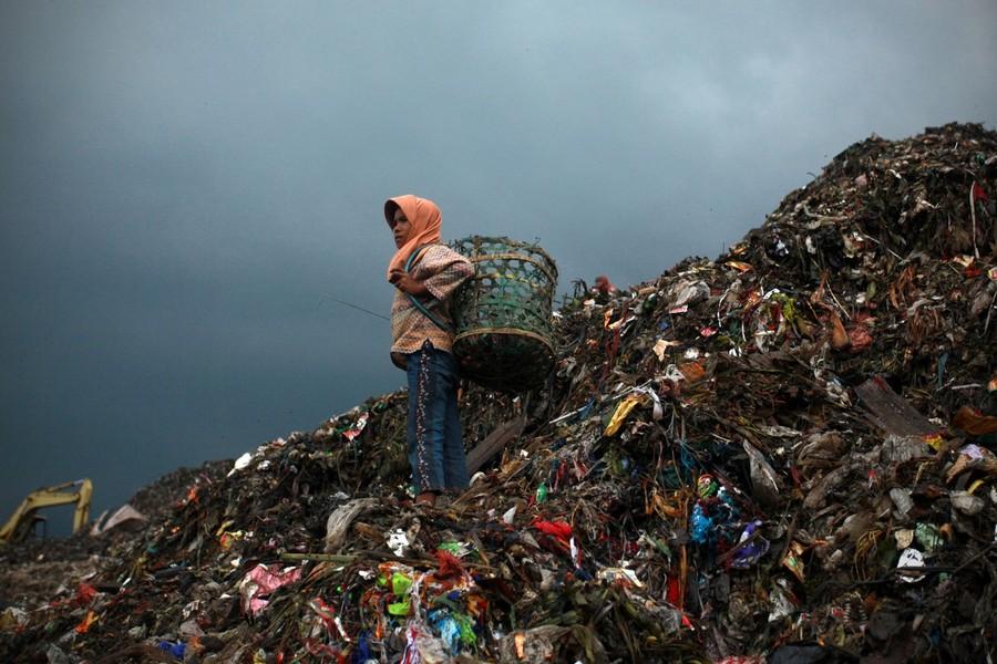 5) 11-летняя Нанг собирает пластик на одной из куч мусора на свалке Бантар Гебанг.