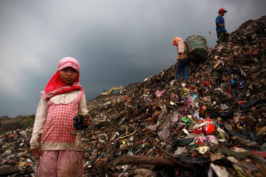3) 9-летняя Арсинах разбирает мусор вместе с другими детьми.