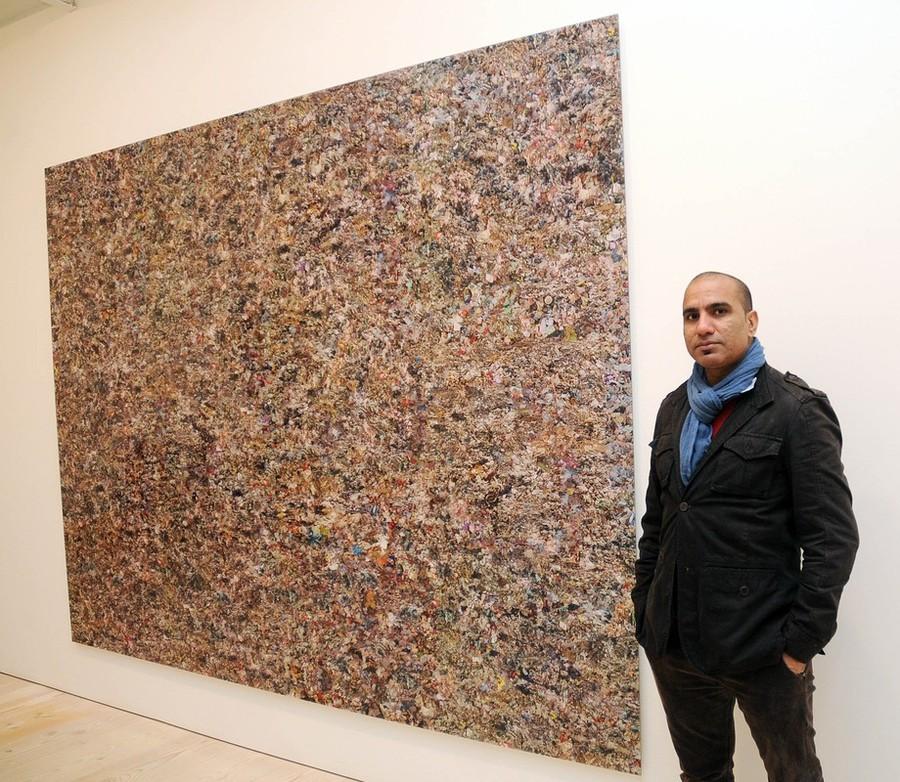 2) Художник Рашид Рана (Rashid Rana) позирует на фоне своей работы.
