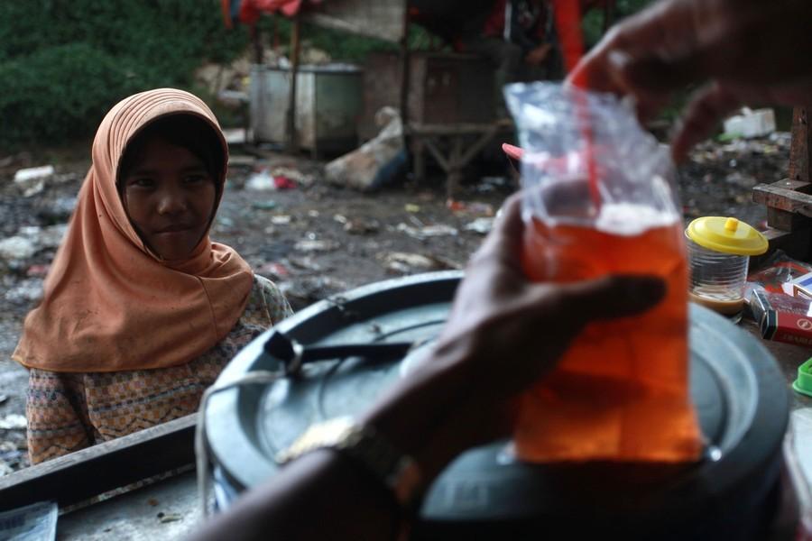 21) 11-летняя Нанг покупает себе напиток, после долгих часов работы на свалке.