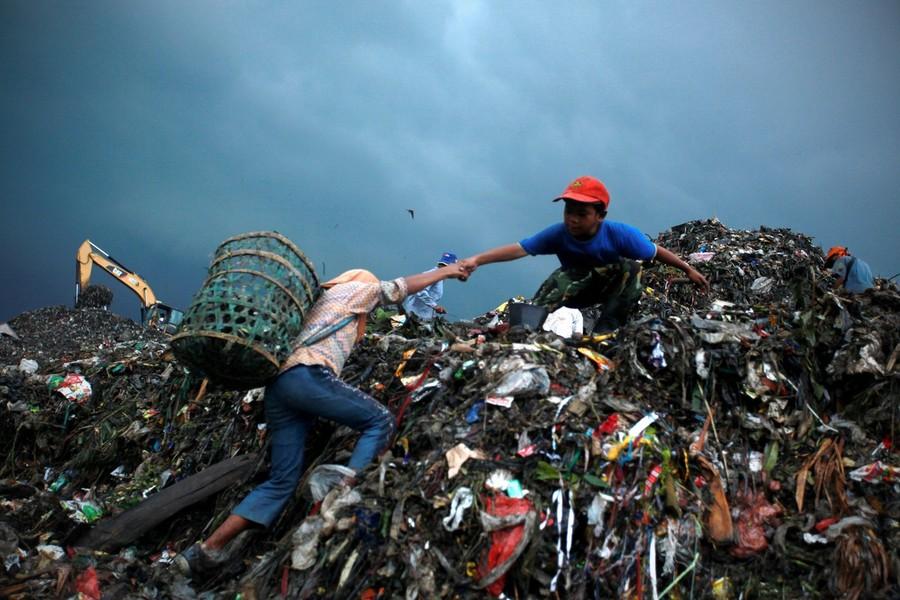 """19) 8-летний Басир помогает своей маленькой """"коллеге"""", 11-летней Нанг взобраться на огромную кучу мусора."""