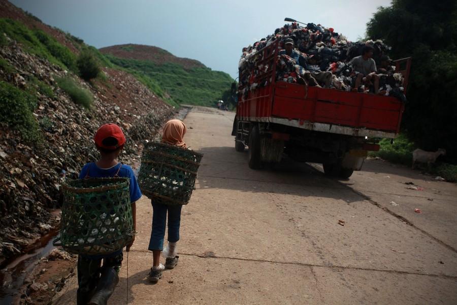 """16) 8-летний Басир и 11-летняя Нанг с корзинами за плечами идут вслед за мусоровозной машиной по направлению к свалке, на ежедневную """"работу""""."""