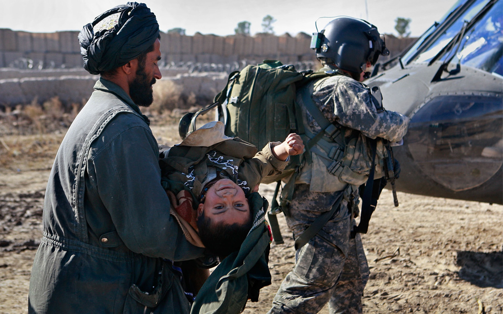 5) Афганец несет своего сына, чье тело свело судорогой, в вертолет «MEDEVAC» за сержантом- медиком Аароном Берроусом из Амарилло, штат Техас, 17 декабря 2009 года недалеко от Дели, Афганистан. (Scott Olson/Getty Images)