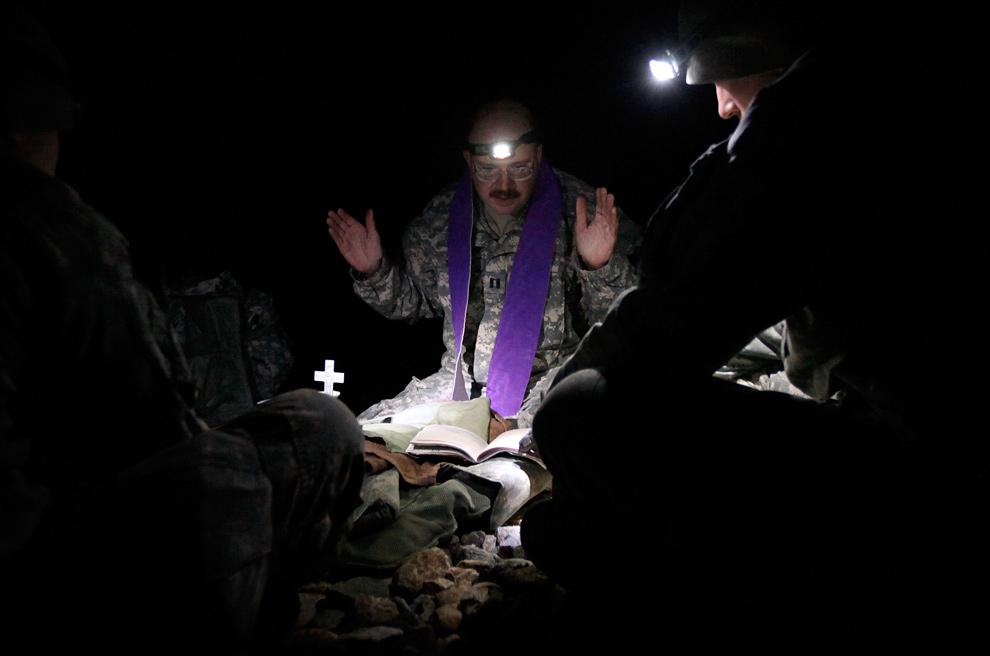 8) Армейский священник отец Карл Сублер из Версаля, штат Огайо, проводит католическую службу на посадочной площадке для вертолетов, пока солдаты ждут прибытия вертолета на передовой оперативной базе «Росомаха» 12 декабря 2009 года недалеко от Калата. Большая часть солдат на площадке – солдаты из пехотных войск четвертого батальона – возвращается домой на двухнедельный отпуск перед годовым отправлением в Афганистан. (Scott Olson/Getty Images)