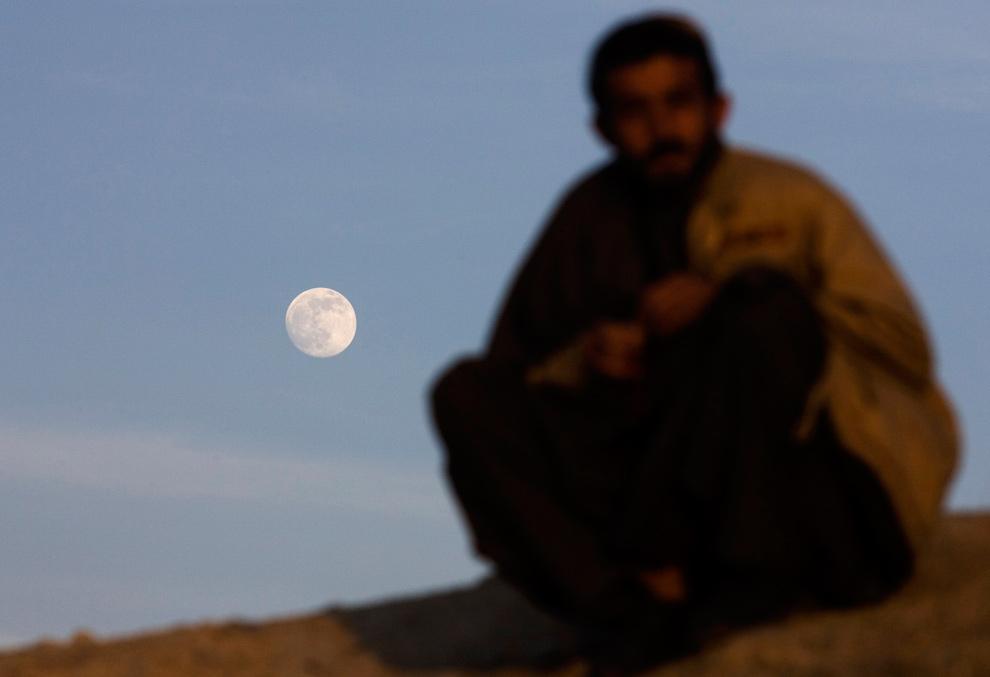 10) Афганец сидит на холме на фоне нарастающей луны в Кабуле 30 декабря 2009 года. Завтра луна станет полной, и это будет вторым полнолунием на 31 декабря, известным как «тринадцатое полнолуние». Следующее «тринадцатое полнолуние» произойдет 31 августа 2012 года. (REUTERS/Marko Djurica)