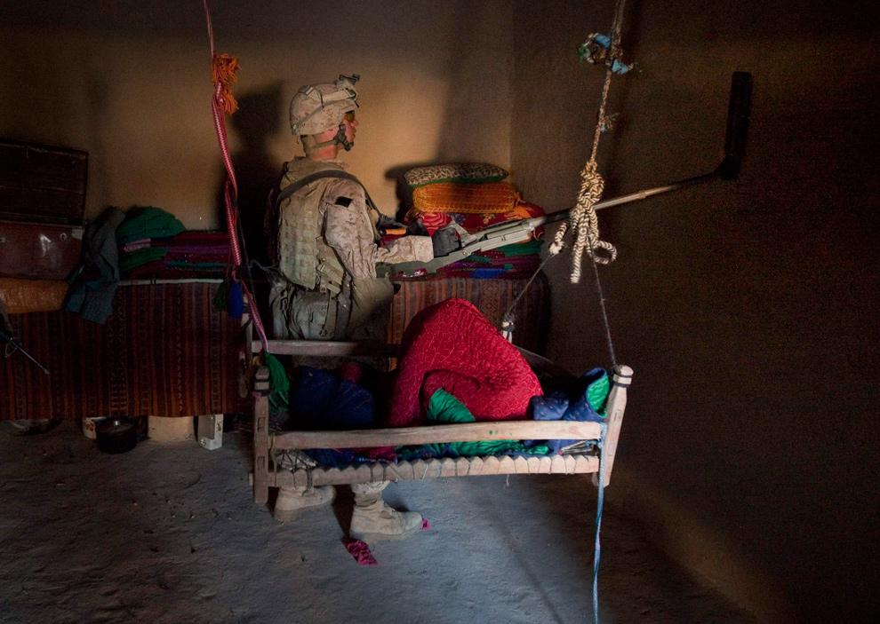 12) Морпех из второго батальона из Кэмп Лежун, Северная Каролина, использует металлодетектор рядом с детской кроваткой во время зачистки в округе Гармсир провинции Гильменд 17 декабря 2009 года. (REUTERS/Adrees Latif)