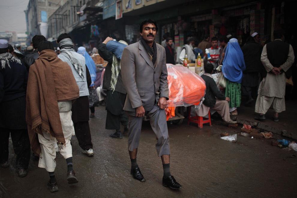 13) Мужчина придерживает штанины, чтобы не забрызгать их на грязном рынке на окраине Кабула 2 декабря 2009 года. (AP Photo/Alexandre Meneghini)