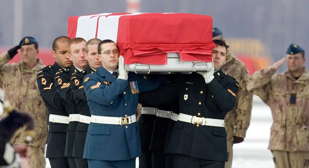 15) Почетный караул несет гроб с телом лейтенанта Эндрю Р. Наттала к ожидающему катафалку на базе Канадских вооруженных сил 28 декабря 2009 года. Лейтенант Натталл погиб, когда рядом с ним сдетонировало самодельное взрывное устройство на юго-западе города Кандахар 23 декабря 2009 года. (REUTERS/Fred Thornhill)