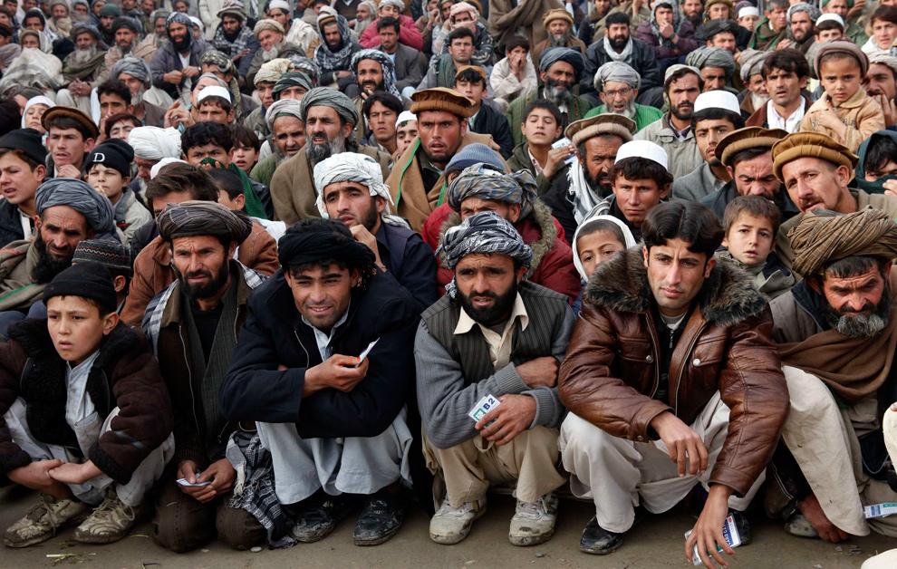 """16) Мужчины ждут начала раздачи бесплатной провизии немецкой благотворительной организацией """"KinderBerg International"""" в центре Кундуза 19 декабря 2009 года. (REUTERS/Fabrizio Bensch)"""