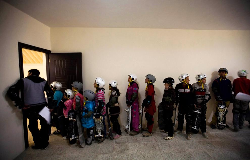 """18)  Афганские дети стоят в очереди, чтобы попасть в скейтборд-парк в Кабуле 29 декабря 2009 года. Недавно в Кабуле открылся """"Skateistan"""" – первый скейтбординг-парк и школа в Афганистане. Десятки детей и подростков – от детей министров до уличных хулиганов – заинтересовались скейтбордом, и правительство надеется, что открытие школы и парка для катания на скейтбордах позволит держать детей подальше от улиц. (REUTERS/ Marko Djurica)"""