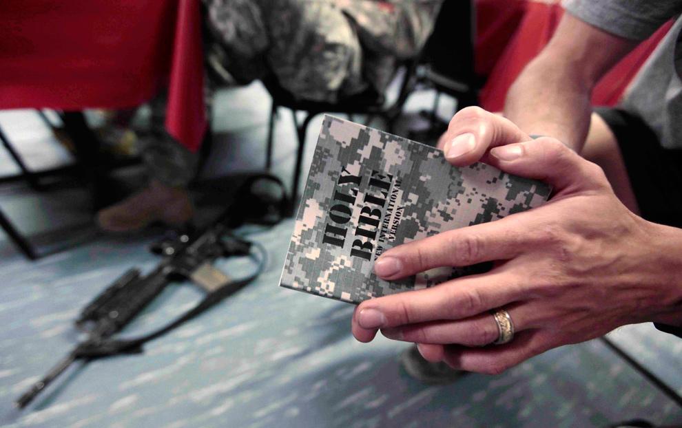 20) Солдат оперативной группы Denali 1-40 CAV держит библию во время христианской службы на передовой оперативной базе в провинции Ковст 13 декабря 2009 года. (REUTERS/Zohra Bensemra)