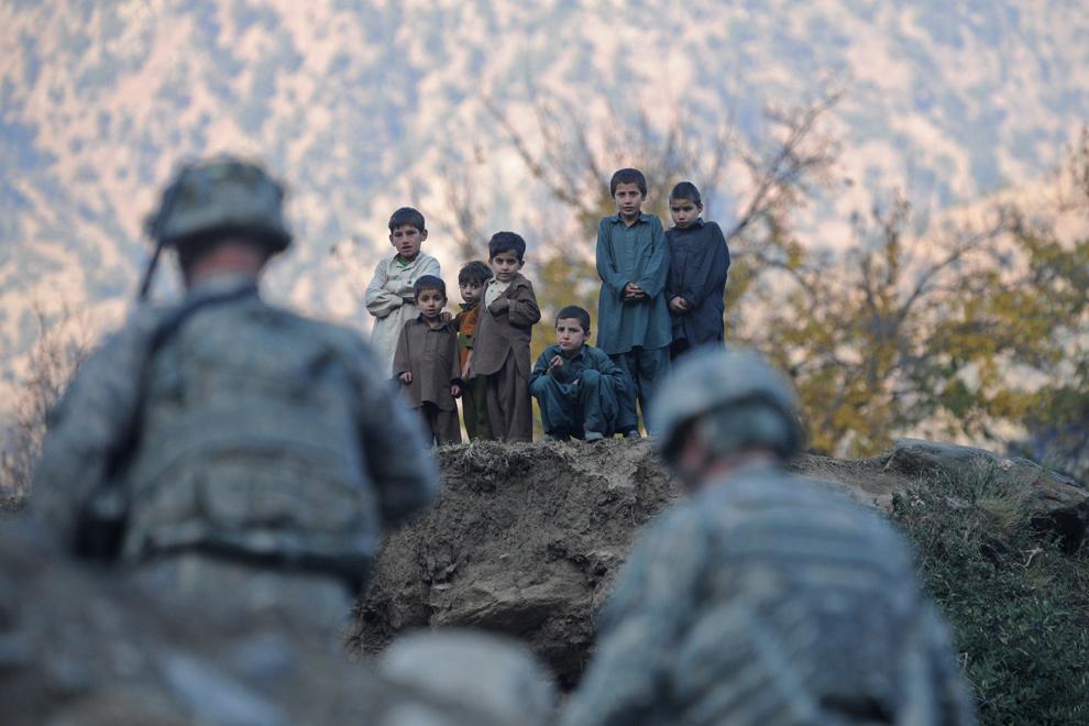 21) Афганские дети смотрят на солдат из первого батальона 32-ого пехотного полка третьей бригады 10-го горного дивизиона, патрулирующих деревню Шигал в провинции Кунар на востоке Афганситана 7 декабря 2009 года. Конвой, направившийся в деревню, чтобы переговорить со старейшинами, попал под обстрел реактивного противотанкового гранатомета. (TAUSEEF MUSTAFA/AFP/Getty Images)