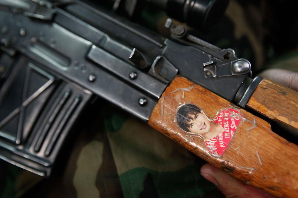 24) Солдат Афганской национальной армии держит фотографию болливудского актера Шахида Капура на рукоятке своего оружия на передовой оперативной базе «Рашмор» 28 ноября 2009 года недалеко от Шарана. На передовой базе, где также располагаются и американские войска, осталось совсем немного солдат афганской армии – большинство афганцев разъехались по домам на трехдневный праздник курбан-байрам. (Scott Olson/Getty Images)