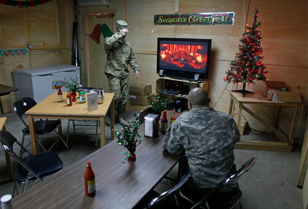 25) Солдат смотрит телевизор в столовой, недавно украшенной к Рождеству, на военном аванпосте Мичиган недалеко от деревни Кандигал в долине реки Пех, провинция Кунар, 21 декабря 2009 года. (AP Photo/Dario Lopez-Mills)