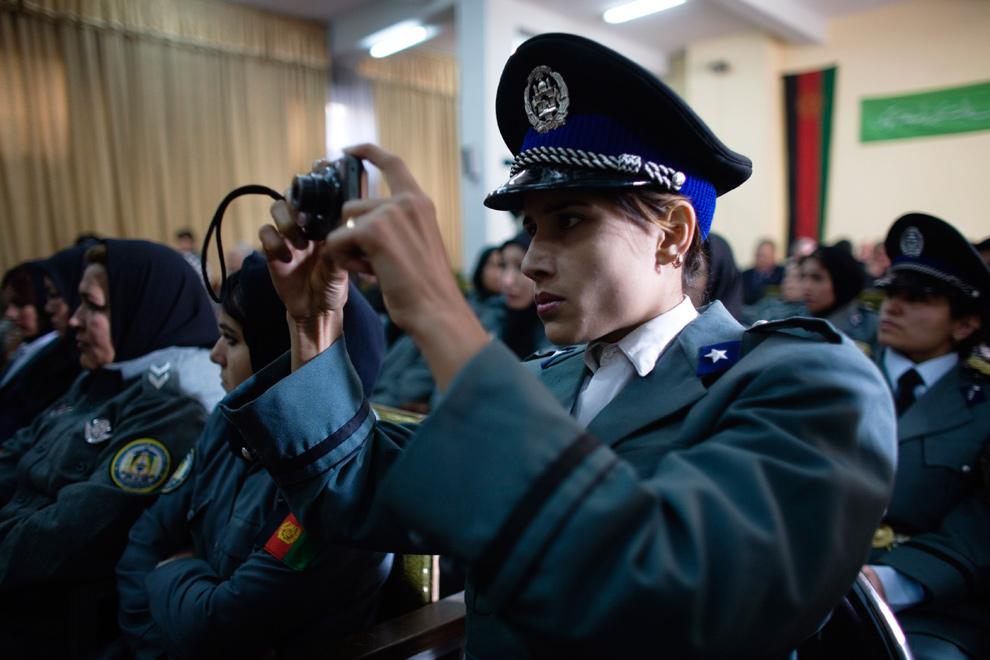 28) Афганская полицейская фотографирует церемонию выпуска после восьми недель тренировок в полицейской академии в Кабуле 17 декабря 2009 года. Только 500 афганских женщин служат в полиции, в то время как мужчин там 92 500. Большая часть женщин служит в относительно спокойных районах, таких как Кабул и северная провинция Герат. Правительство планирует нанять к 2014 году 5000 женщин для службы в офицерских или гражданских войсках. (AP Photo/Dusan Vranic)