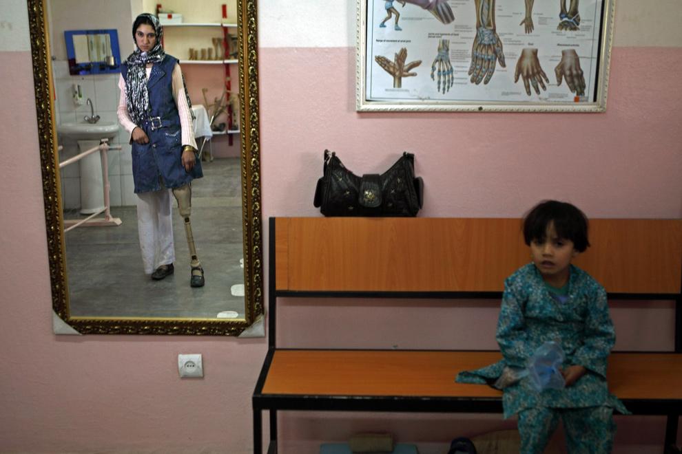 31) Ребенок смотрит, как девушка, наступившая на мину, смотрит в зеркало в Международном реабилитационном центре Красного Креста 10 декабря 2009 года в Кабуле. Реабилитационный центр обучает и восстанавливает людей, пострадавших от мин или деформаций конечностей, чтобы они смогли вернуться в общество и найти работу. Отдел ООН, занимающийся статистикой по происшествиям, связанным с минами, сообщает, что в стране каждый месяц от мин гибнут или получают ранения около 62 человек. (Majid Saeedi/Getty Images)