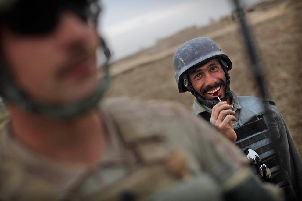 33) Проходящий боевую подготовку афганский полицейский из программы обучения, приводимой американскими войсками морской пехоты, ест чупа-чупс, пока морпехи обыскивают дом, в котором, как сообщалось, находится взрывчатка, во время патруля в Кхан Нешин в провинции Гильменд 8 декабря 2009 года. (AP Photo/Kevin Frayer)
