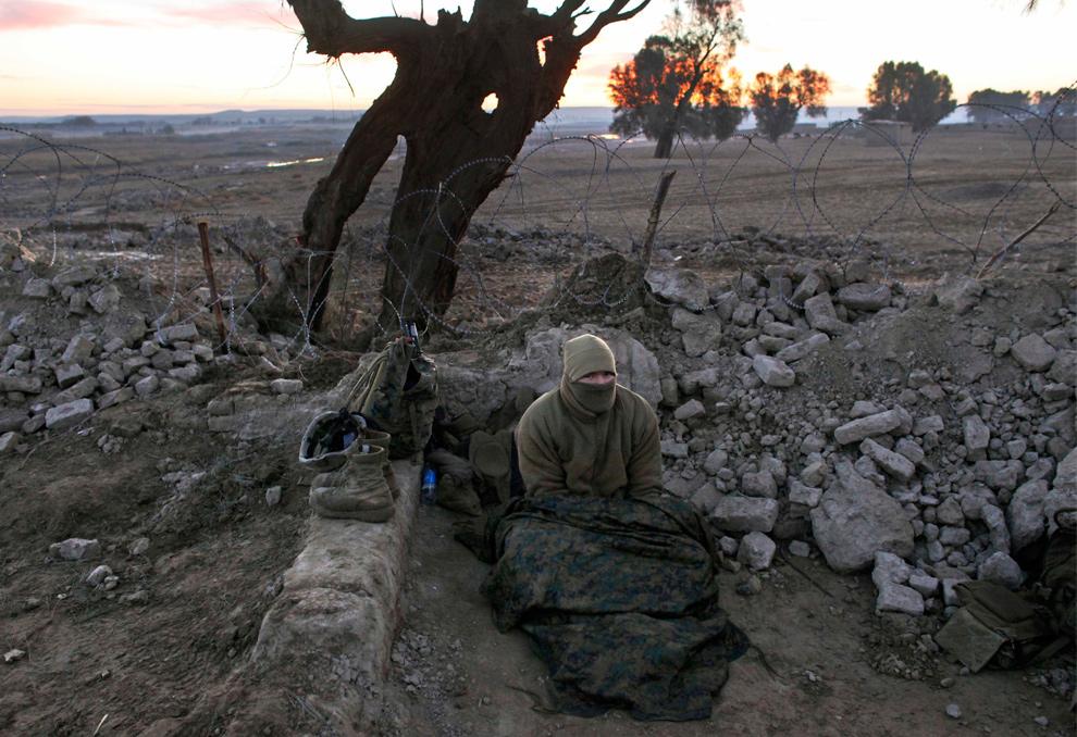 34) Морпех из второго батальона пытается согреться, проснувшись холодным утром во время операции в округе Гармсир провинции Гильменд 18 декабря 2009 года. (AP Photo/Kevin Frayer)