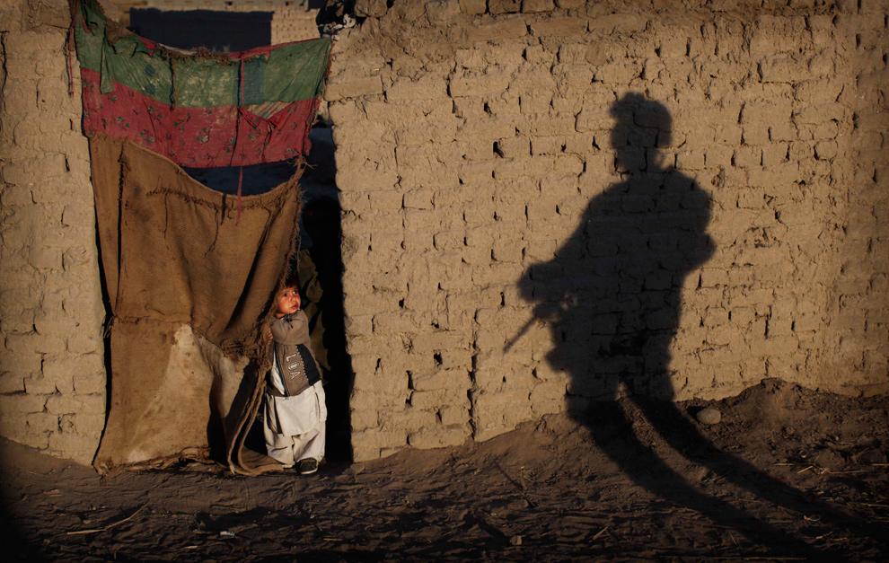 35) Афганский ребенок смотрит из проема дверей рядом с тенью морпеха из второго батальона во время операции в округе Гармсир 18 декабря 2009 года. (AP Photo/Kevin Frayer)