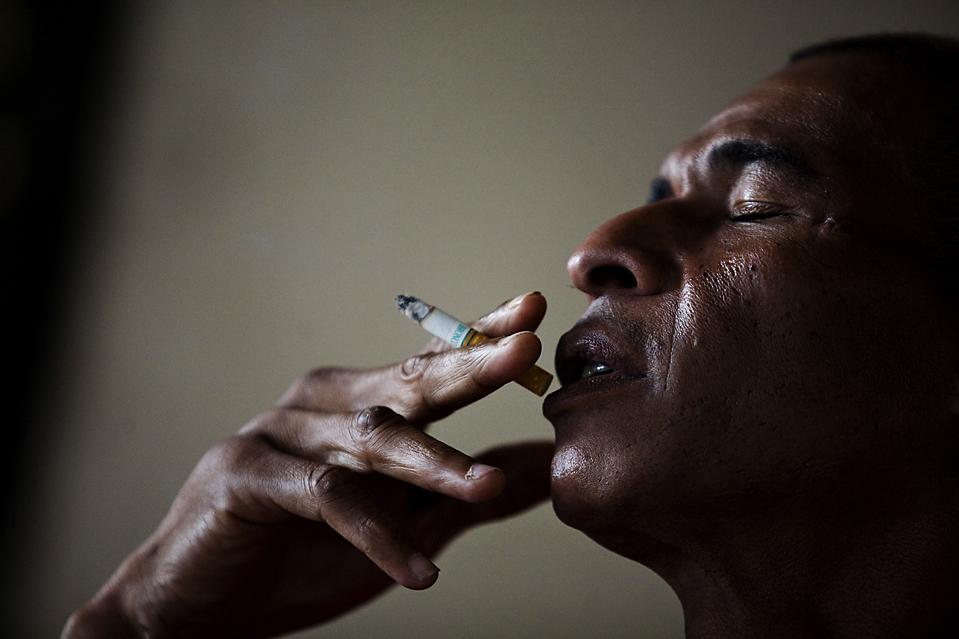 1. Марк Генри Бигот курит у своего дома в Майями, штат Флорида, 16 января. В тот день его жена Олиния позвонила ему из Порт-о-Пренс, чтобы сказать, что они с дочкой живы, но им нужна помощь. (Jason Henry for The Wall Street Journal)