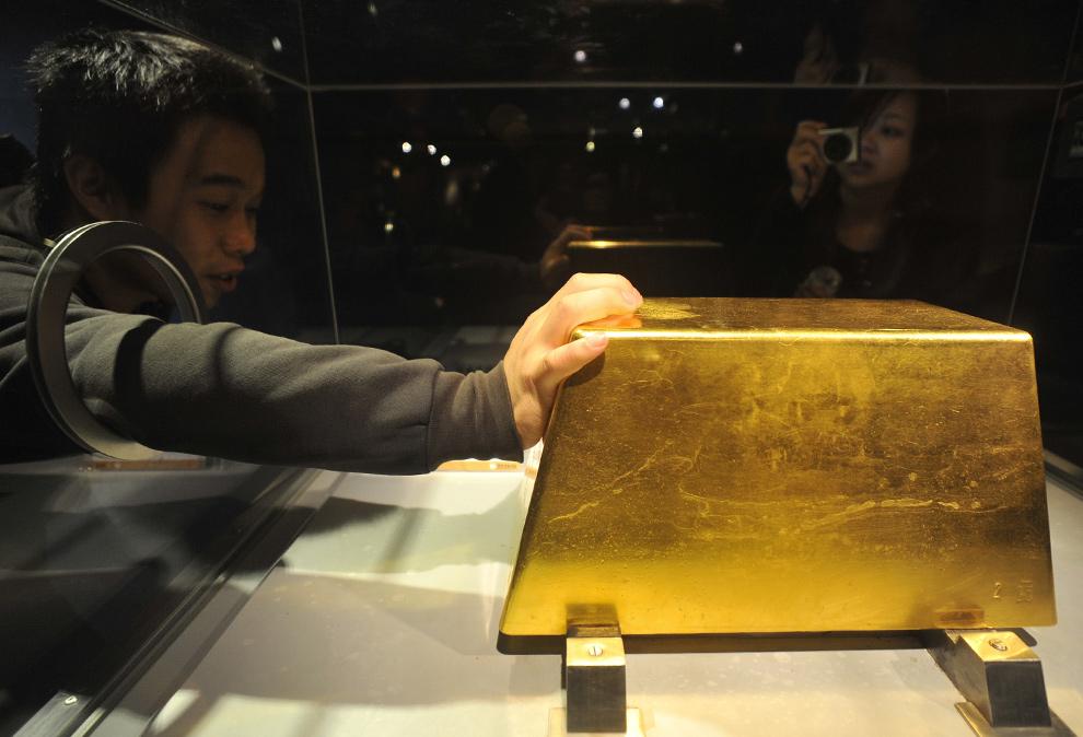 1. Посетитель прикасается к самому крупному куску золота весом 220 кг (стоимостью более 7,8 миллионов долларов) в музее золота Джингуаши в Руифанге, Тайбэй, 2 декабря 2009 года. (SAM YEH/AFP/Getty Images)