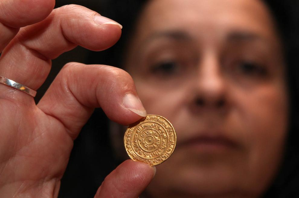 2. Хава Катц – глава отдела сокровищ израильской организации древних находок – держит 1000-летнюю золотую монету, отчеканенную в Египте предположительно в 1095 году н.э. на выставке в археологическом центре Дэвидсона 11 ноября 2009 года. Монету в Иерусалим привезли мусульманские паломники. (GALI TIBBON/AFP/Getty Images)