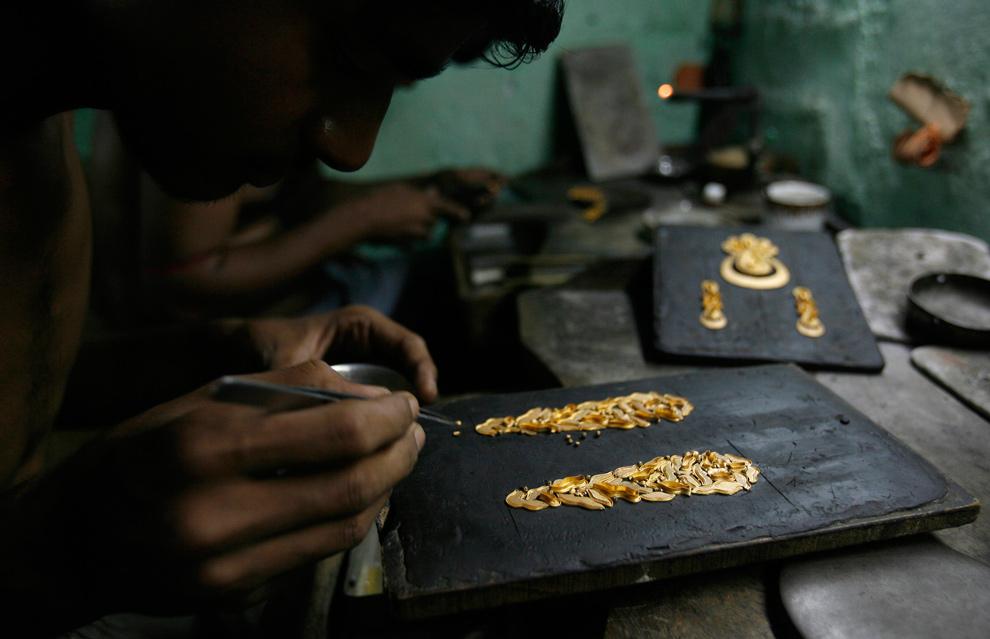 4. Ремесленник делает золотое украшение на заводе по производству ювелирных украшений в восточном индийском городе Калькутта 13 ноября 2009 года. (REUTERS/Parth Sanyal)