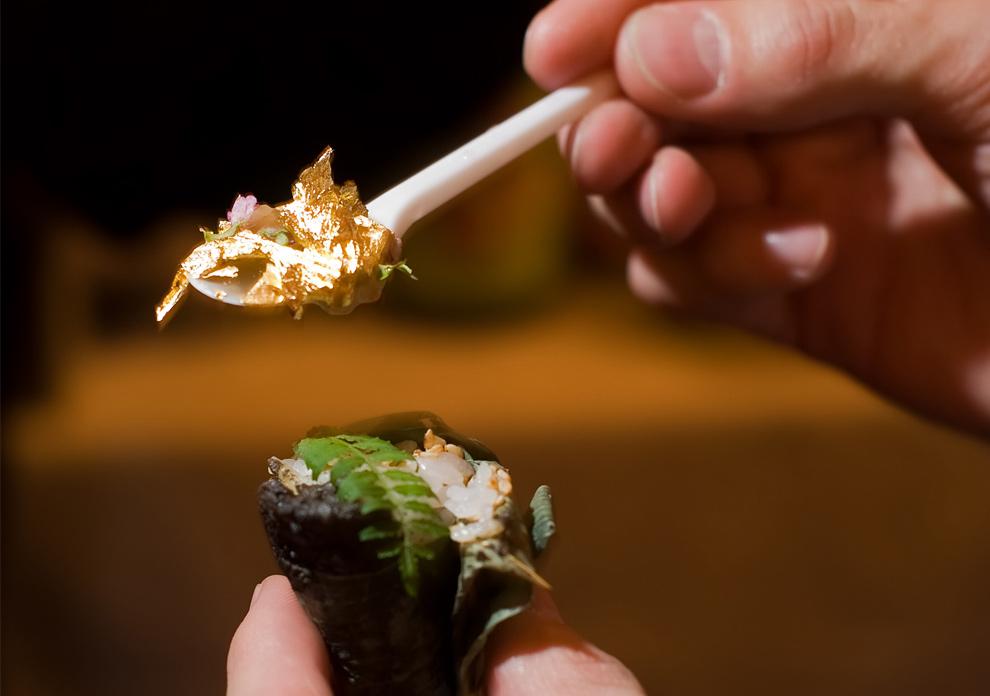5. Мужчина держит ложку с сусальным золотом, которое он собирается съесть с суши на церемонии награждения ресторана «Семь самураев суши» в категории «лучший суши-бар» в Олимпийском выставочном центре в Лондоне 14 ноября 2009 года. Сусальное золото было ингредиентом в меню ресторана-победителя прошлого года «Mitsunori Kusakabe». (LEON NEAL/AFP/Getty Images)