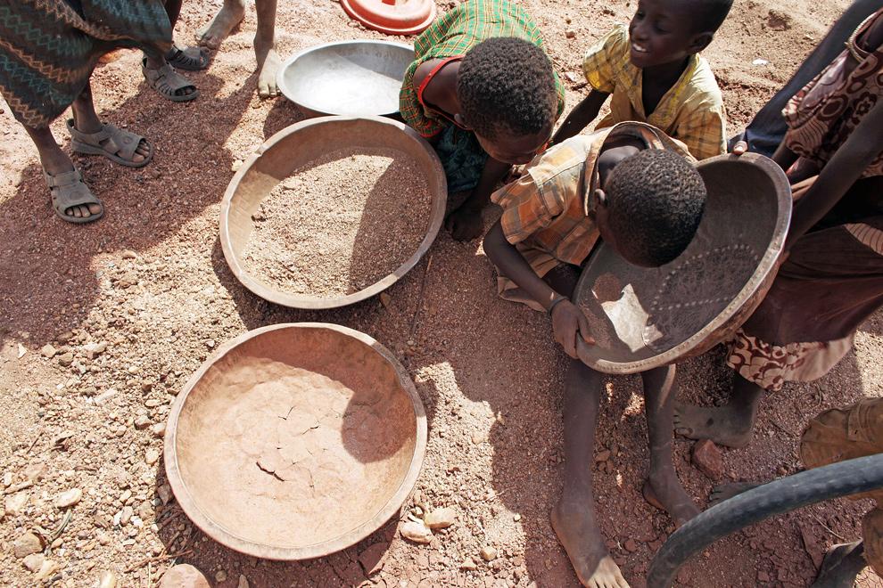 6. Дети из района Туркана промывают крупинки золота, которые помогают выжить их семьям, 9 ноября 2009 года недалеко от Лодвара, Кения. (Christopher Furlong/Getty Images)