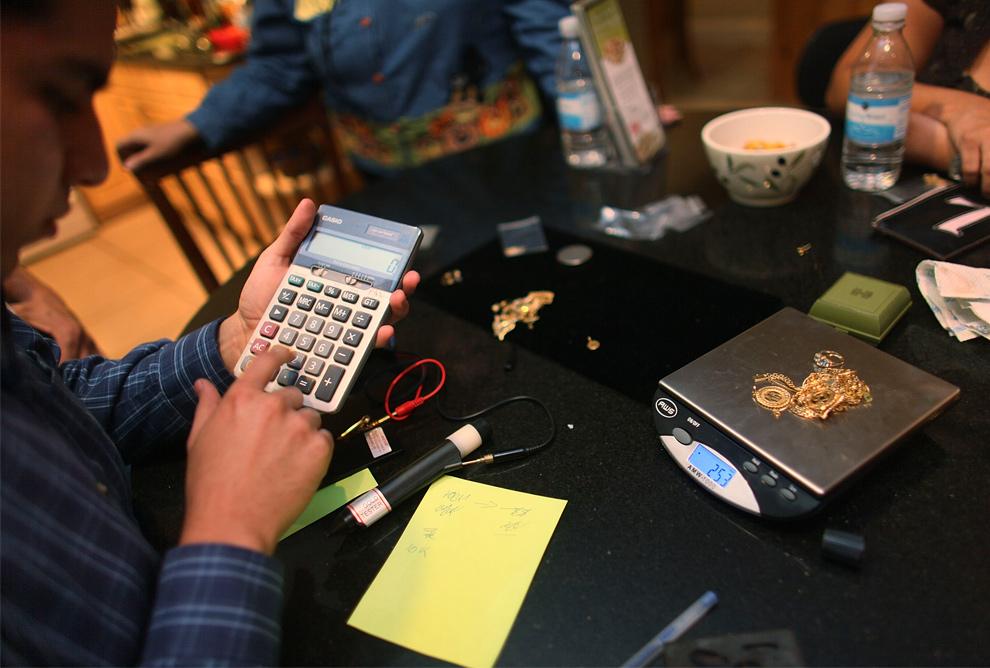 9. Педро Линарес использует калькулятор, чтобы узнать, сколько компания «Fast Cash Gold Parties», на которую он работает, заплатит за золотые украшения на весах 30 октября 2009 года в Хиалеа, штат Флорида. Так как цена на золото остается высокой, компания старается устраивать акции, чтобы людям было выгодно продавать ненужное им золото. (Joe Raedle/Getty Images)