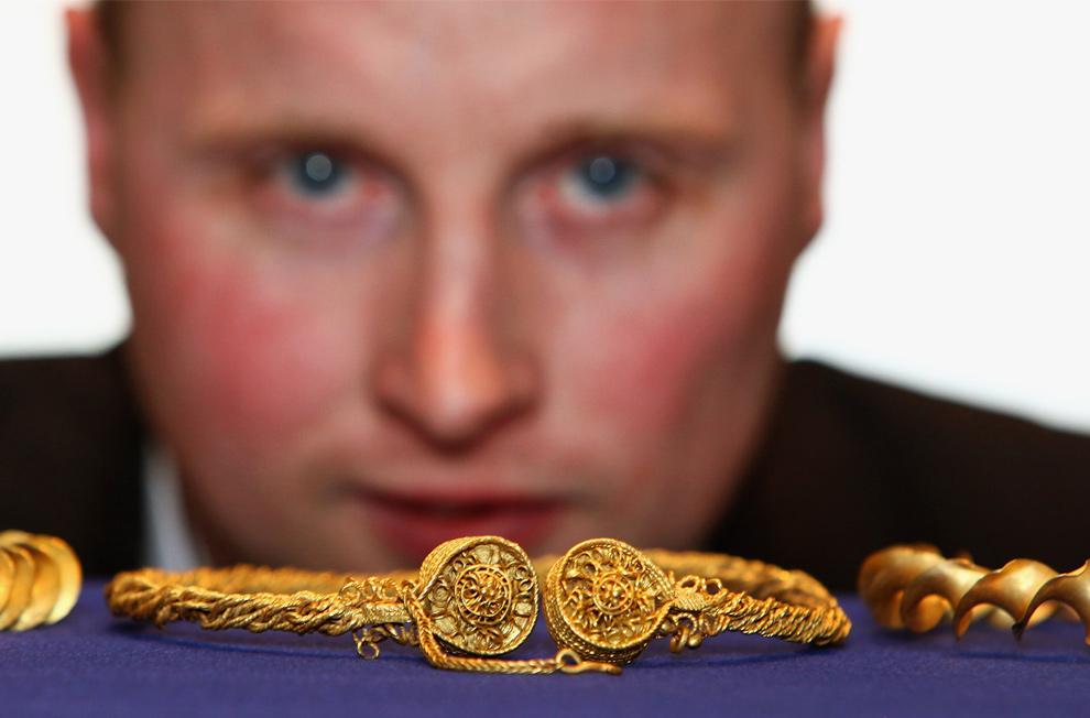 13. Золотоискатель-любитель Дэвид Бут позирует со своими находками эпохи железного века 4 ноября 2009 года в Эдинбурге. Бут нашел золотые кельтские ожерелья на частной территории в Стирлингшире, эти предметы датируются 300-100 до н.э. В данный момент браслеты находятся под защитой Союза кладоискателей. По шотландским законам, все найденные археологические объекты переходят в собственность правительства. (Jeff J Mitchell/Getty Images)