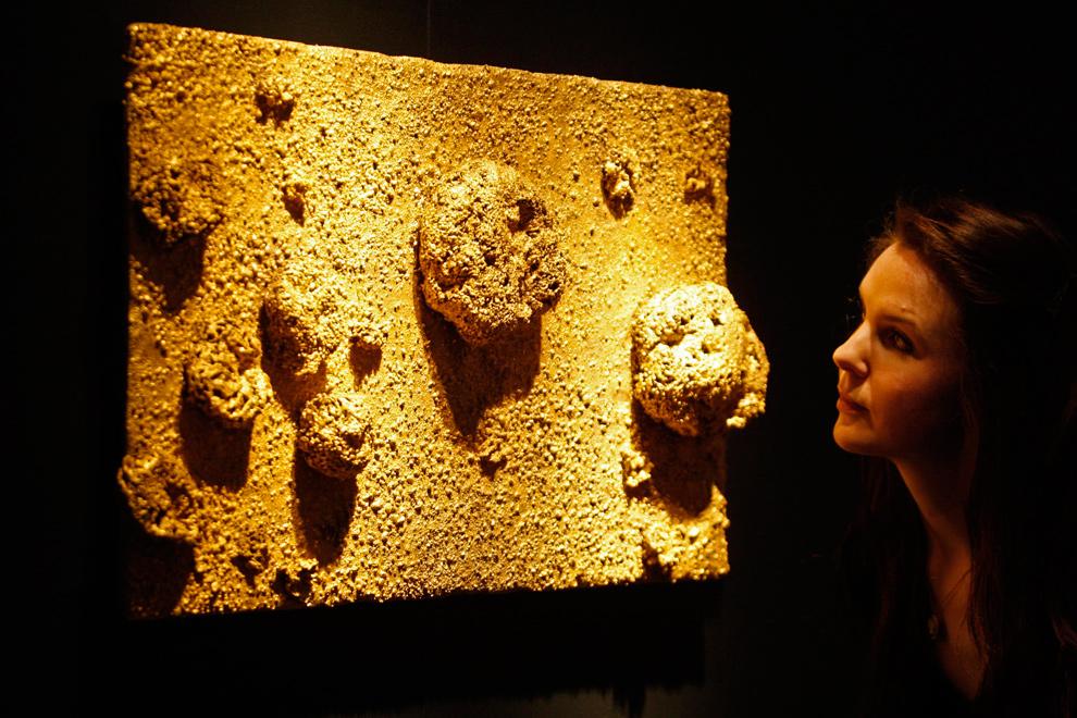 """17. Работник аукциона «Christie's» смотрит на творение Ива Кляйна """"Relief Sponge"""" в Лондоне 20 января 2010 года. Золотая губка будет выставлена на аукцион в секции «Послевоенное и современное искусство» 11 февраля. Ожидается, что произведение будет продано за 5,7 – 8 миллионов евро. (AP Photo/Sang Tan)"""