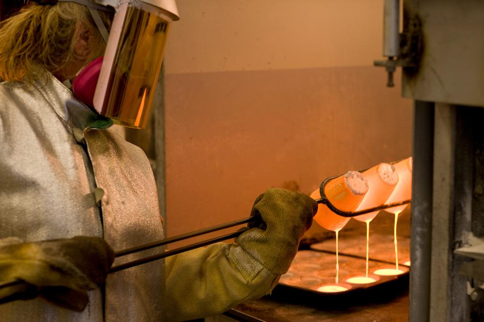 20. Шэрон Брумли выливает расплавленные образцы в формочки, чтобы определить общее содержание золота, на золотодобывающем предприятии «AngloGold Ashanti Ltd. Cripple Creek & Victor» в Колорадо 5 ноября 2009 года. (Matthew Staver/Bloomberg)