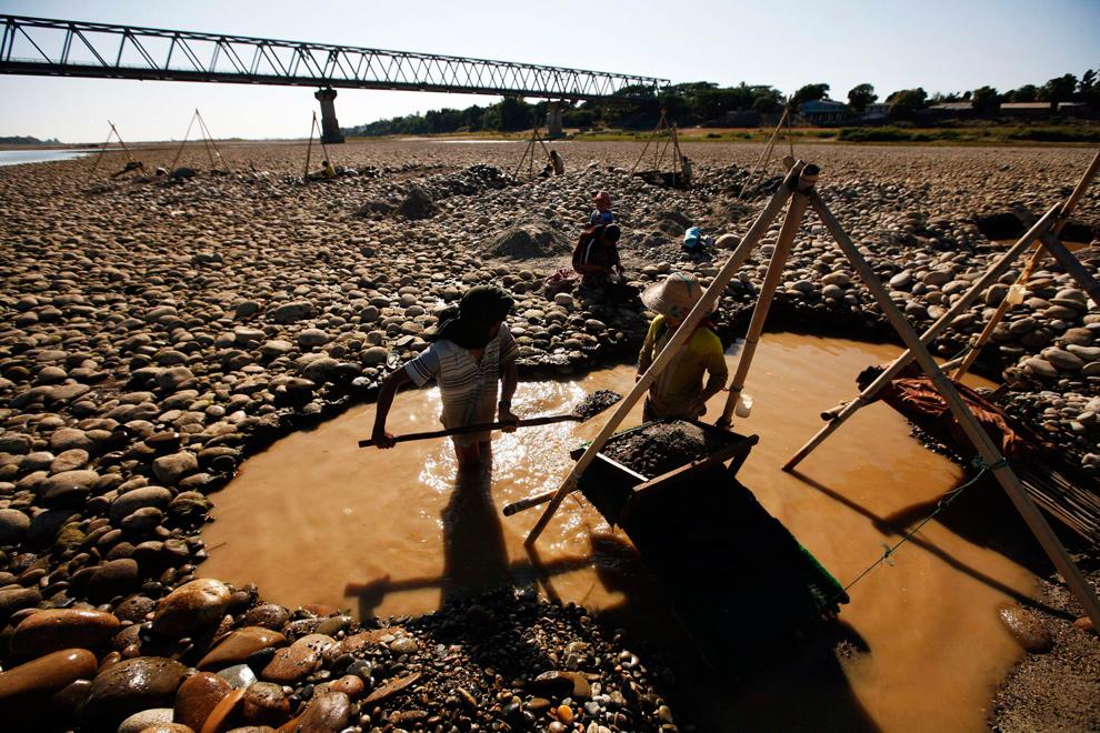35. Жители деревни промывают золото из реки Иррамадди недалеко от моста Бахалминхтин у города Мииткийна, северная Мьянма, 7 января 2010 года. (REUTERS/Soe Zeya Tun)