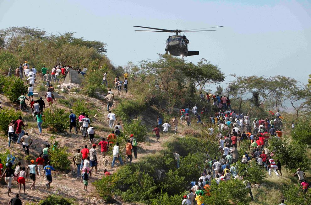 1. Люди бегут к вертолету США недалеко от сельского клуба, используемого в качестве передовой базы 82- ой ВДД США в Порт-о-Пренс 16 января 2009 года. Власти и деблокировочные группы сосредоточены на передаче помощи выжившим после землетрясения гаитянам. (AP Photo/Jae C. Hong)