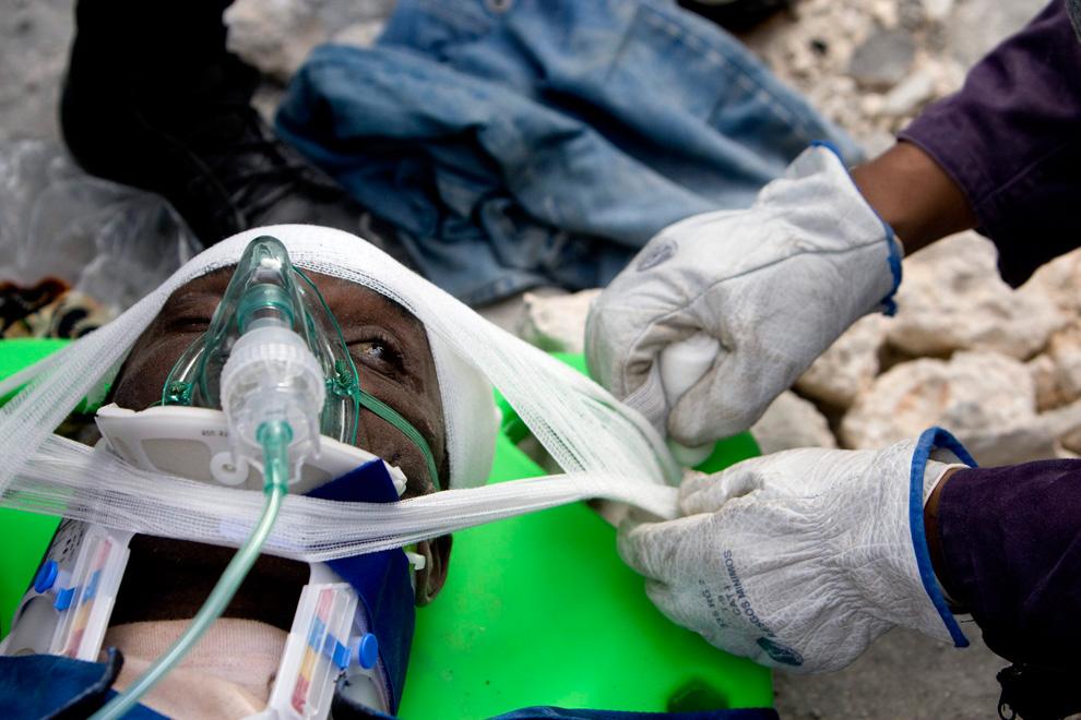 2. Спасатели из США, Испании и Тайваня помогают мужчине в Порт-о-Пренс 17 января 2010 года. (REUTERS/Marco Dormino/MINUSTAH/Handout)