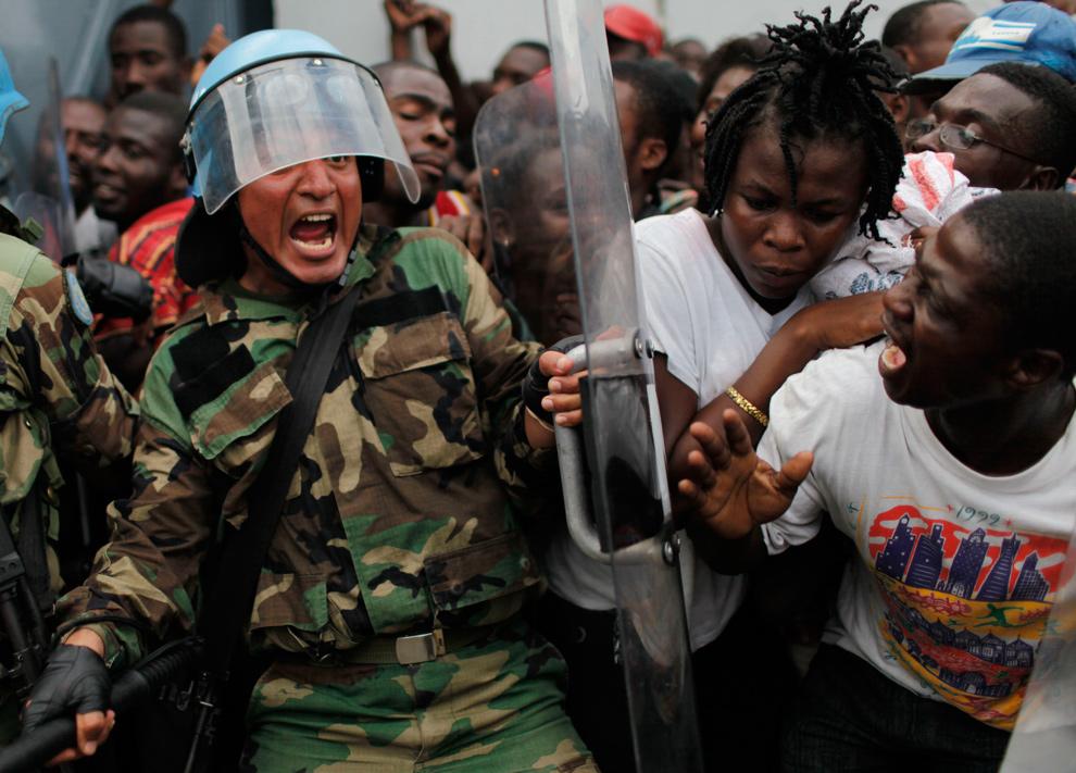 2. Перуанский миротворец кричит, пытаясь сдержать толпу во время раздачи еды на складе в Порт-о-Пренс 19 января 2010 года. (AP Photo/Ariana Cubillos)