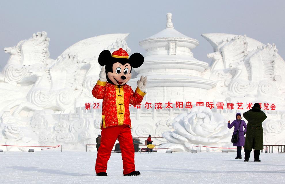 3. Человек в костюме Микки Мауса позирует перед скульптурой из снега в парке Харбина 5 января 2010 года. (REUTERS/Aly Song)