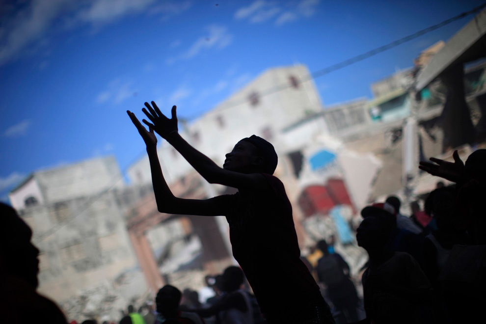3. Женщина во время мародерства разрушенного после землетрясения магазина в Порт-о-Пренс 16 января 2010 года. (REUTERS/Carlos Barria)
