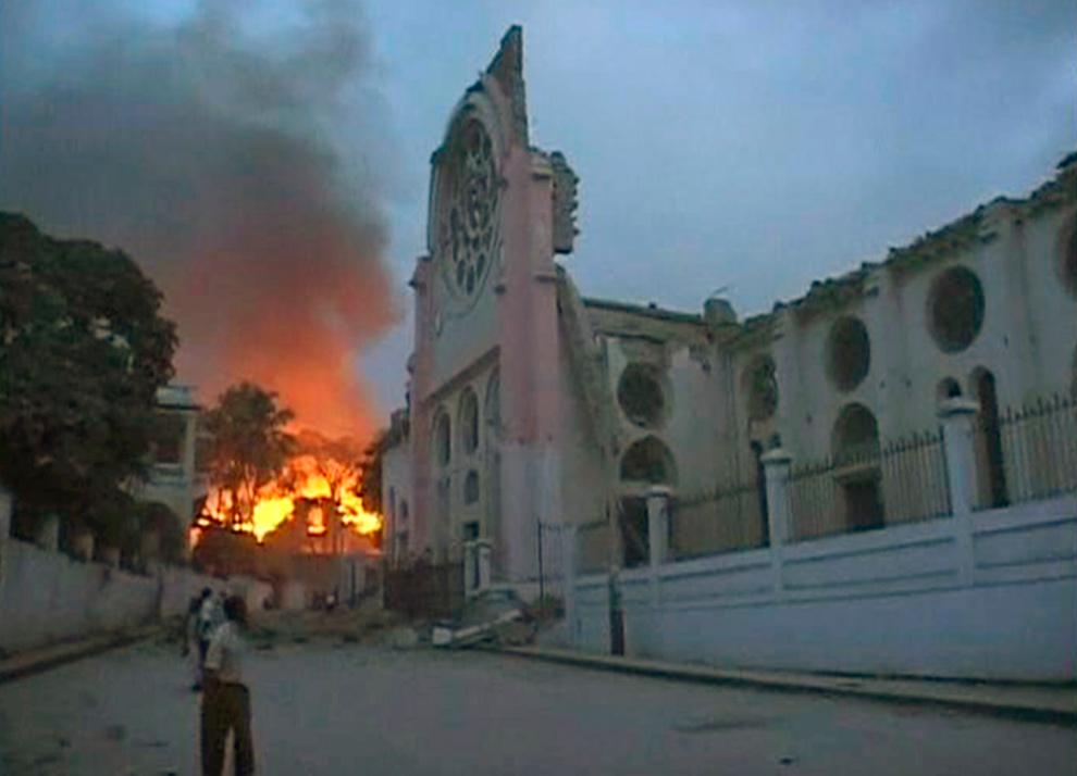 3. Пожар разгорелся недалеко от здания, поврежденного сильным землетрясением, в Порт-о-Пренс 12 января. (REUTERS/Reuters TV)