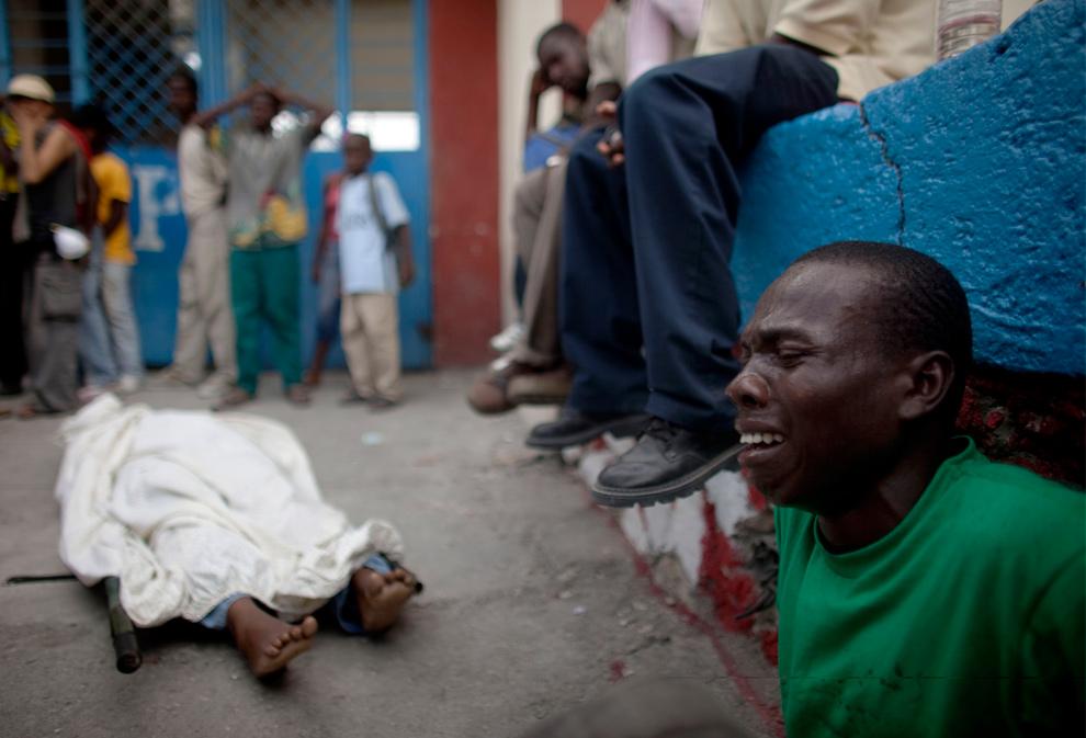4. Мужчина скорбит над телом родственника, скончавшегося после того, как его вытащили из-под обломков здания, в Порт-о-Пренс 19 января 2010 года. (Uriel Sinai/Getty Images)