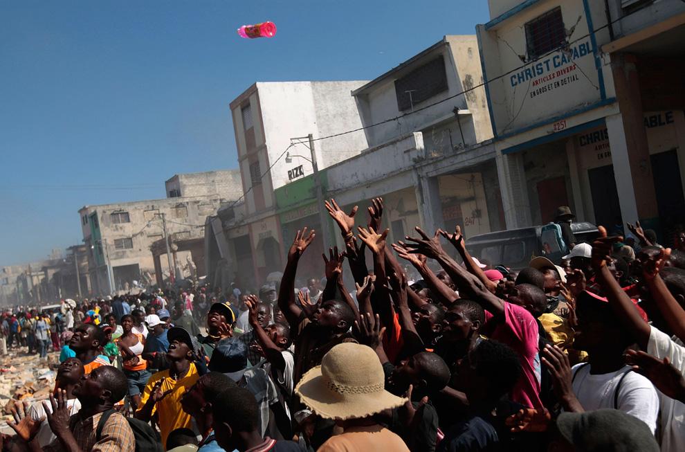 5. Толпа гаитян тянется к продуктам, бросаемым из ближайшего магазина в деловом центре Порт-о-Пренс 17 января 2010 года. (Chris Hondros/Getty Images)