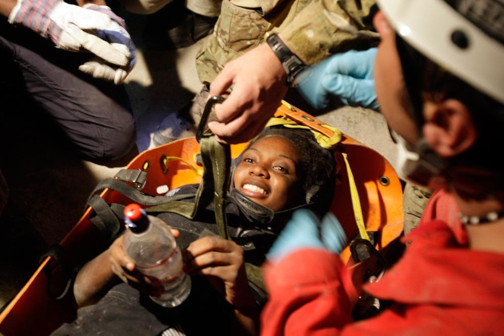 7. Пережившая землетрясение 6-летняя Хоттелин Лозама улыбается, пока французские спасатели вытаскивают ее из-под обломков в Порт-о-Пренс 19 января 2010 года. (AP Photo/Francois Mori)